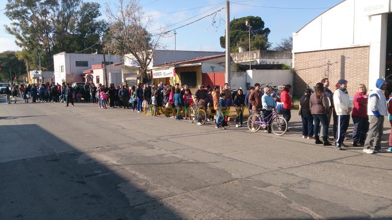 Una larga fila de gente que esperaba por un litro de leche